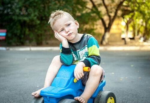 En liten gutt på en leketøybil