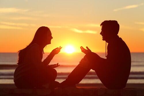 Vit hvordan du skal uttrykke deg selv: Par sitter på stranden ved solnedgang