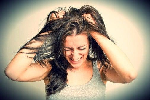 kvinne drar seg i håret