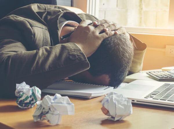 frustrert mann ved et skrivebord med krøllet opp papir
