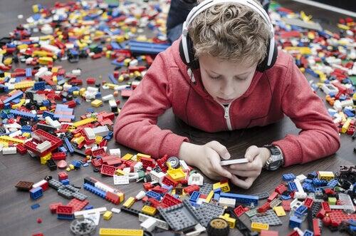 Gutt med lego, hodetelefoner og telefon