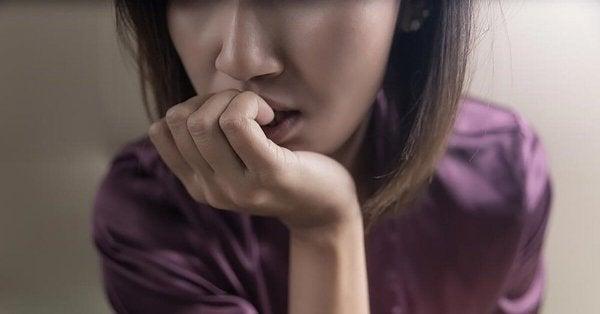 En nervøs kvinne som biter negler