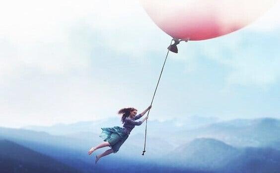 en jente som holder seg til en gigantisk ballong over fjellene