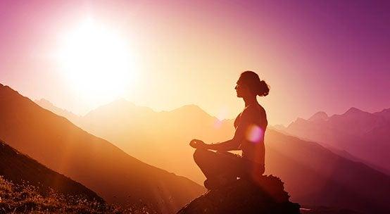 En kvinne som gjentar mantraer i fjellet