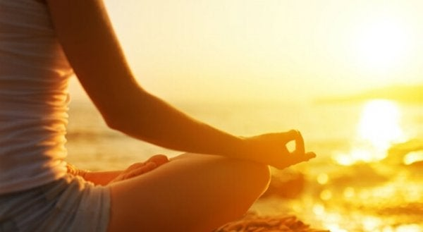 Kvinne mediterer på stranden
