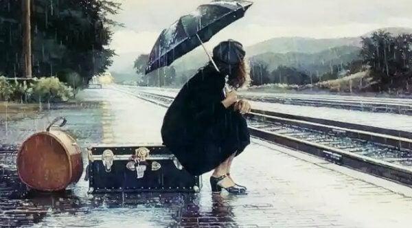 Kvinne sitter på koffert under paraply