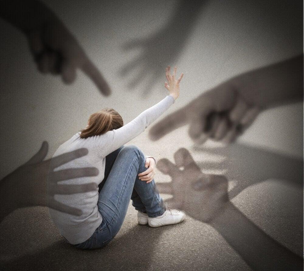 Mange gigantiske hender peker på en jente på bakken.