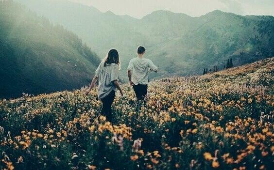 To personer som vandrer i et fjell fylt med blomster