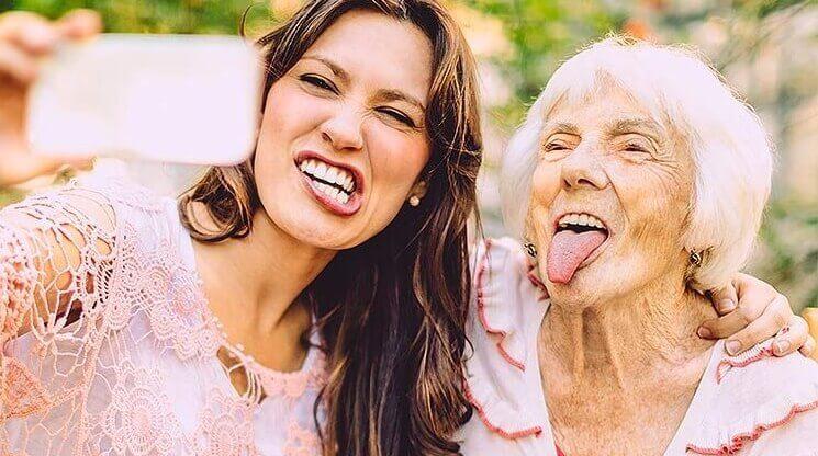 en eldre kvinne og en ung kvinne som tar en selfie