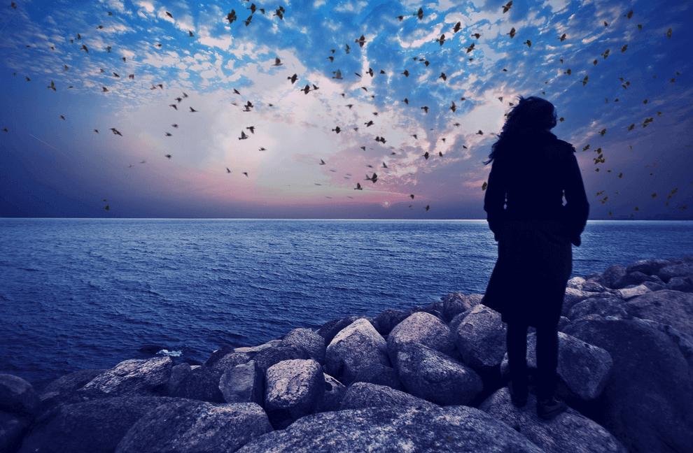 Kvinne på steinstrand ser utover havet