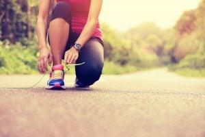Kvinne på joggetur knytter skoen