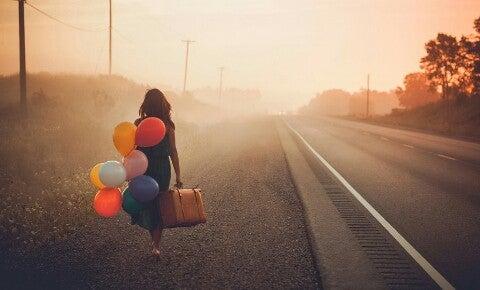 Kvinne med ballonger og koffert kan se håp i mørket