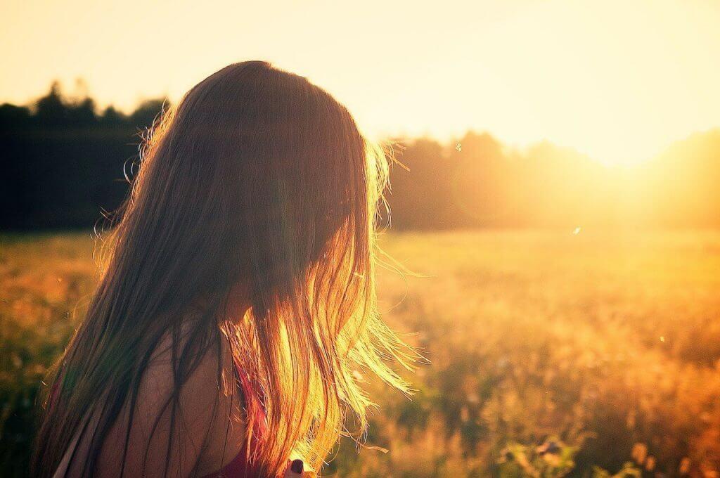 Lykkelig jente ute i solnedgangen