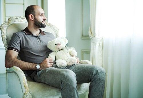 Mann som holder en bamse ser ut av vinduet