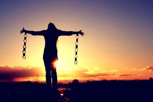 Kvinne med ødelagte lenker i solnedgang