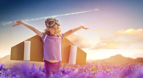 Et lykkelig barn med pappvinger som et fly