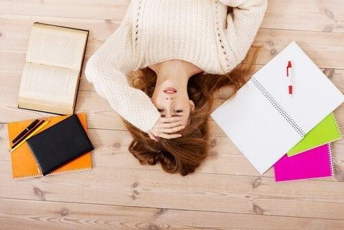 Sliten kvinne på gulvet med bøker