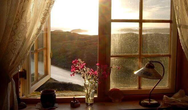 Et åpent vindu som viser et vakkert landskap.