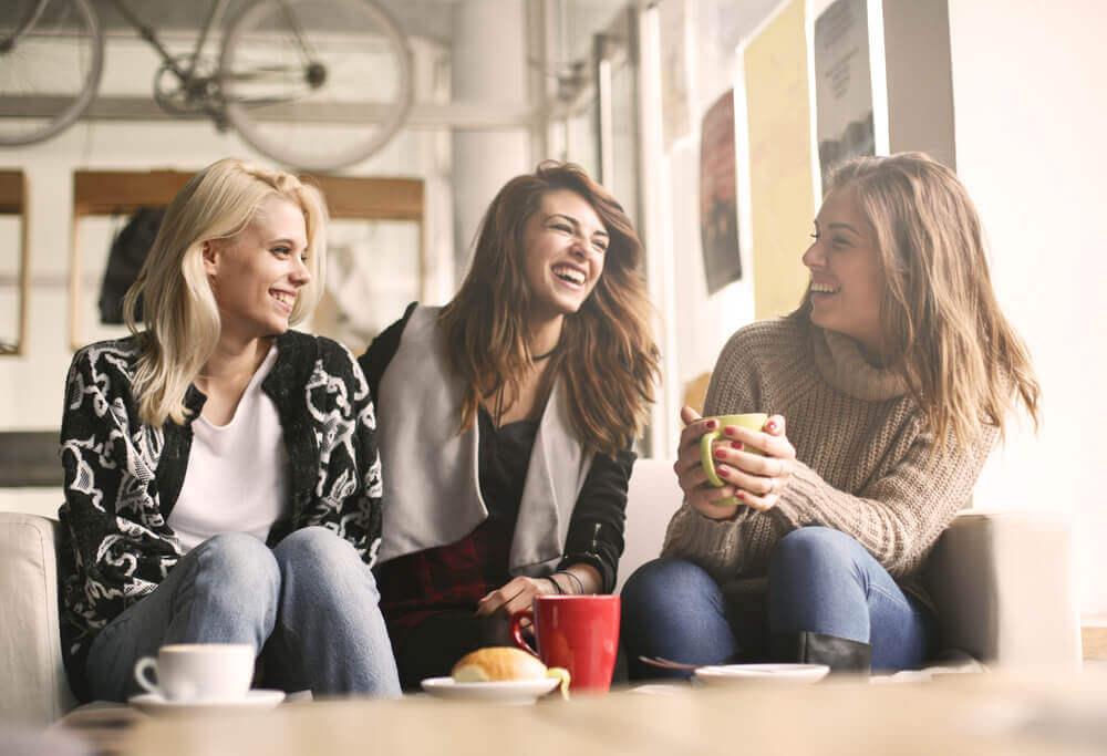 Tre venninner som ler