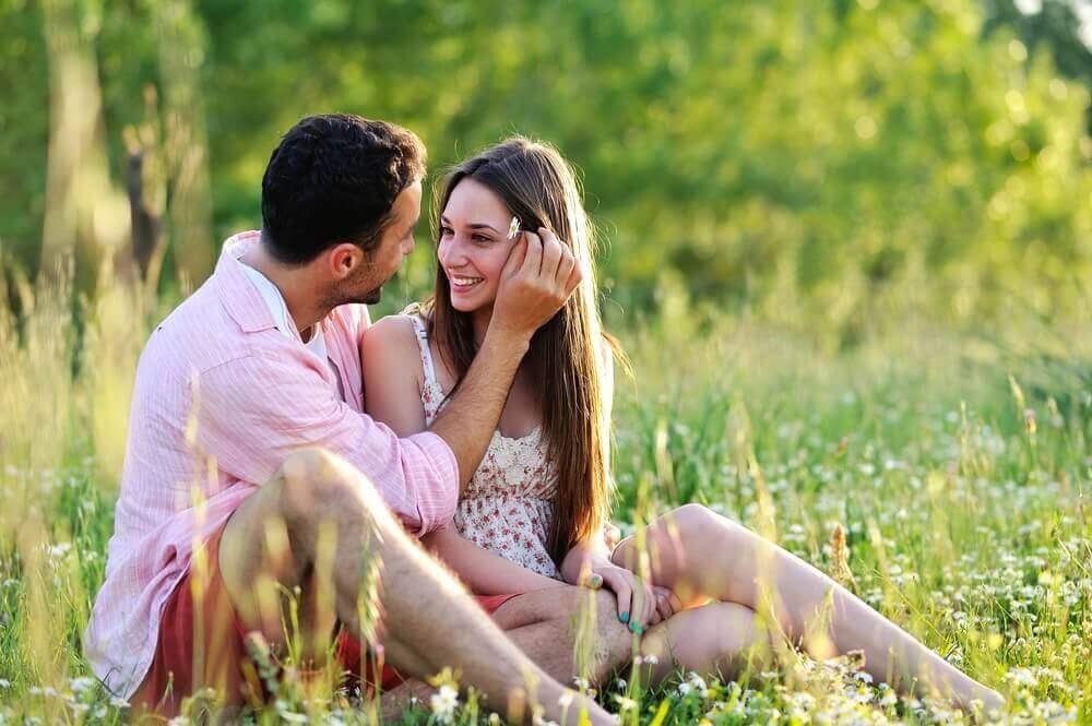 Forelsket par sitter i gresset
