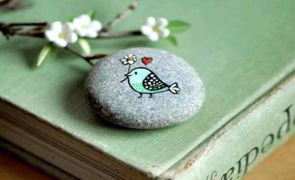 En fugl som bærer en blomst, malt på en stein.