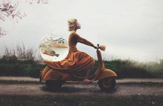 En kvinne på en scooter med en fiskebolle