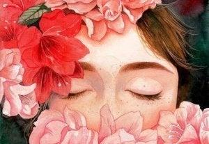 Jente som har blomster rundt seg