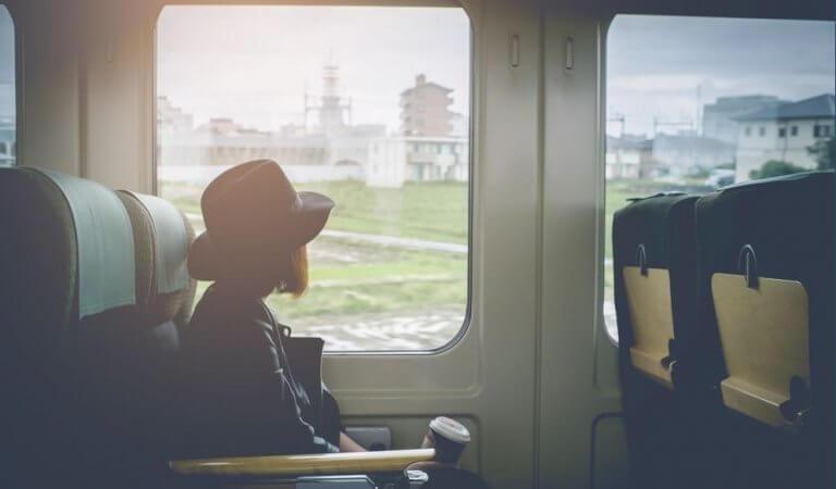En jente sitter ombord på et tog.