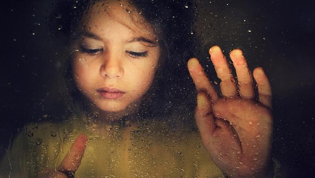 En trist liten jente tegner på et regnfullt vindu.
