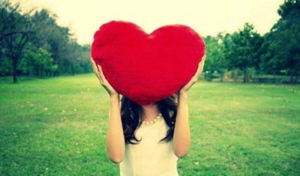 En kvinne som holder et stort, rødt hjerte over hodet sitt