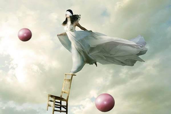 Kvinne balanserer på en stol med rosa baller i luften