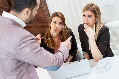 Mannlig sjef diskuterer med to kvinnelige ansatte