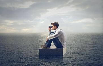 Mann sitter på koffert på havet og ser i en kikkert