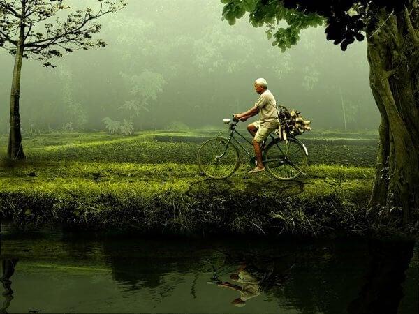 Du kan gjøre det: en eldre mann som sykler ved en dam.