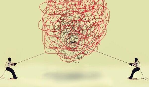 To personer trekker i to tråder for å løse en floke