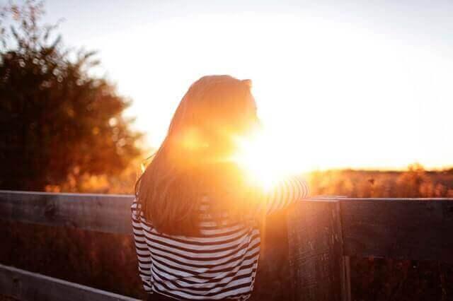 Kvinne som ser på solnedgangen