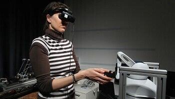 Kvinne kontrollerer en robot