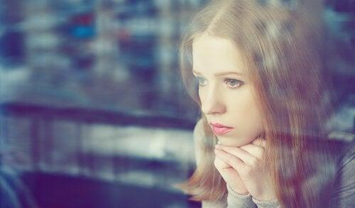 Bekymret kvinne ser ut vinduet