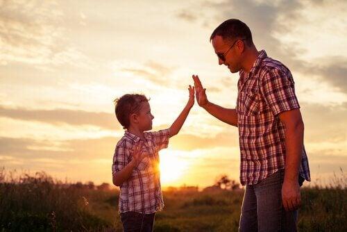 Glad far og sønn i solnedgang.