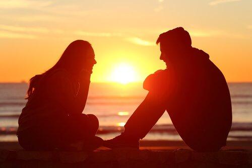 To venner snakker og lytter ved solnedgang.