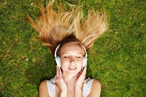 Jente ligger i gresset og lytter til musikk