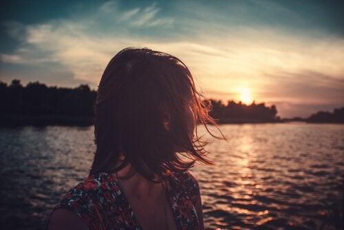 Kvinne som vender hodet mot havet