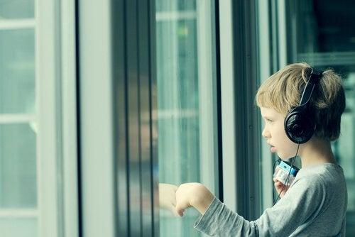 Liten gutt med aspergers som lytter til musikk