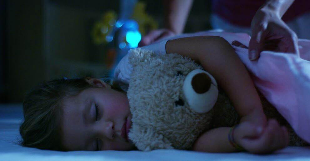 En liten jente som sover med kosebamsen sin