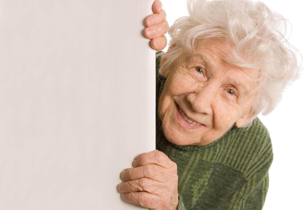En eldre kvinne smiler.