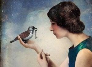 En kvinne holder en fugl med en nøkkel i munnen