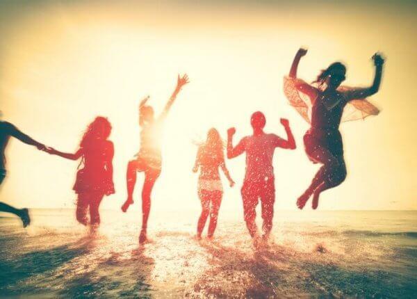 venner hopper lykkelig i bølgene