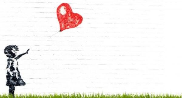 En liten jente vil si farvel til sin røde hjerteballong.