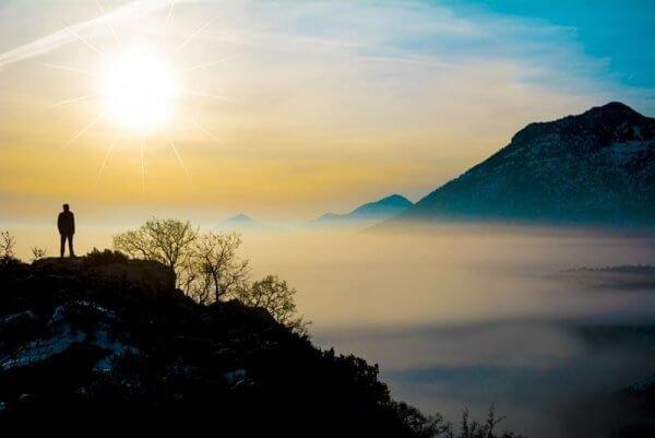 En mann på et fjell som praktiserer mindfulness