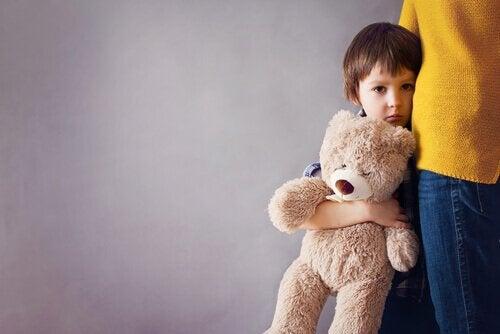 Trist gutt søker trøst hos moren og holder en bamse